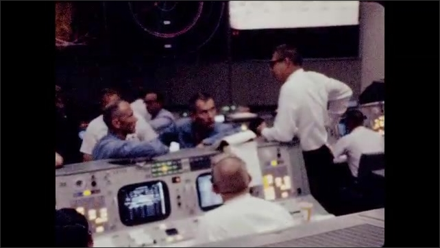 1960s: Man by control panel talks to man in jumpsuit. Men seated at monitors. Men talking over control panel. Men talking over control panel, men loom at monitors.