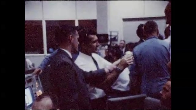 1960s: Fade in, close up of equipment. Man holds folded piece of paper, man puts hand in paper. Men talking, man holds folded paper, zoom in on paper.