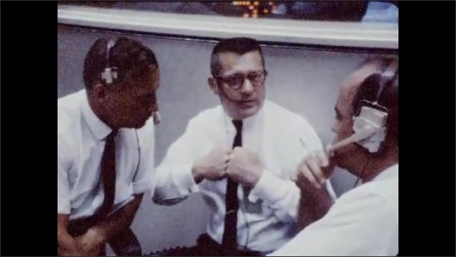 1960s: Man talking to other man, moves fists in air. Man talking, moves fists. Long shot, men at control panels, zoom in on man.