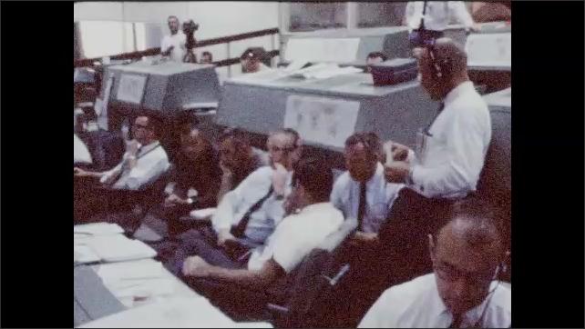 1960s: Man standing at control panel, talks to seated man. Men seated at panel, look at monitors. Men talking.