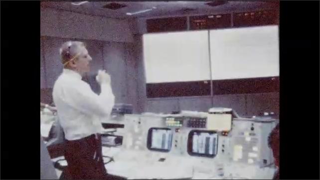 1960s: Rear view, man looking at monitors, man turns and walks past camera. Man standing at control panel smoking.