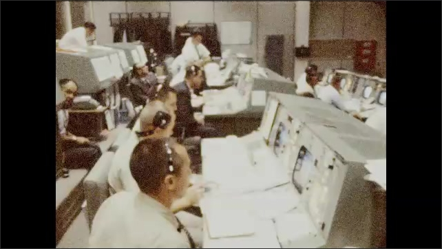 1960s: Close up of man. Men at control panel. Man looks at papers next to seated man.