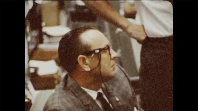 1960s: Men seated at control panel. Close up of man. Men seated, looking at monitors.