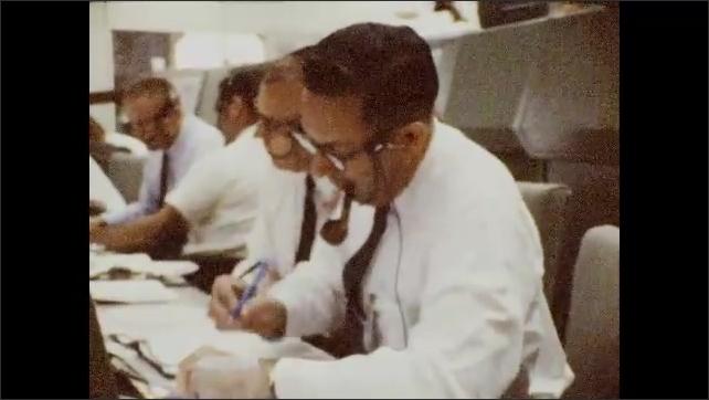 1960s: Men talking, look at monitor. Man at control panel, writing.