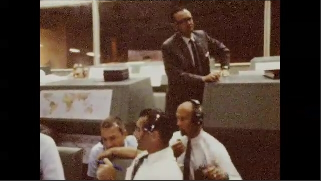 1960s: Close up of Neil Armstrong talking. Men talking, zoom out. Man at control panel, zoom in on man writing.