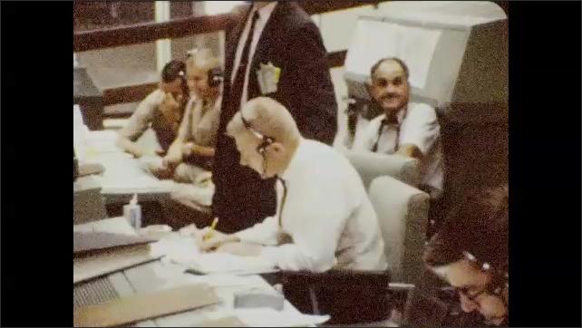 1960s: Men at control panels. Men at control panel, look at monitors, man stands. Men talking.