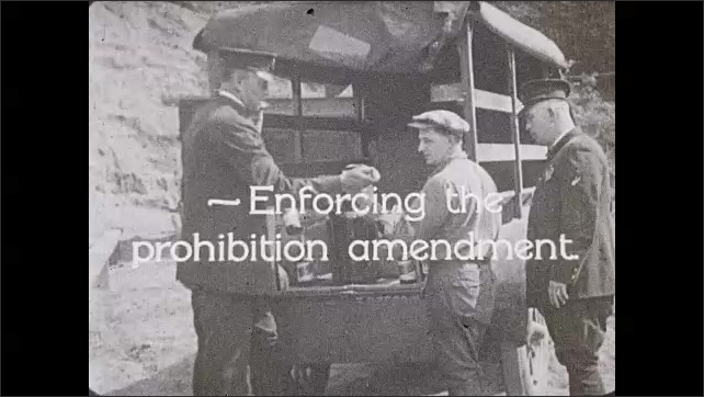 """1930s: Policemen stop and search a truck. Policemen find liquor. Text """"Enforcing the prohibition amendment"""". Policemen break bottles of liquor with hammers."""