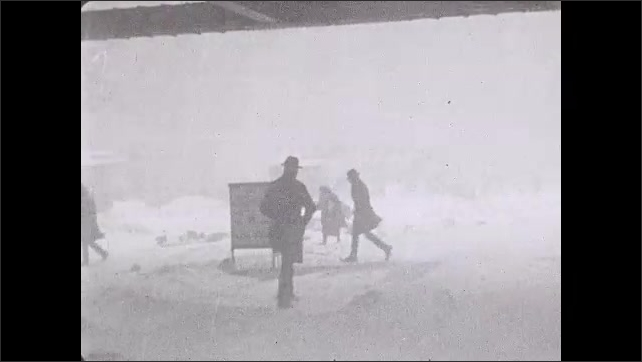 """1930s: People rush in the blowing snow. Newspaper blows in the blizzard wind. Intertitle """"down in Key West, Florida, people are using fans to keep cool"""". Women walk in sun under parasols."""