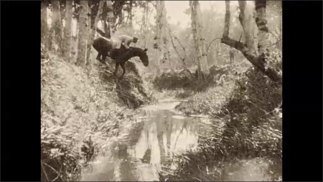 1930s: Uniformed men on horseback, agile horses jump off riverbank across stream. Fearless horses slide down steep hillside.