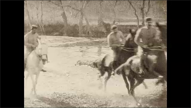 1930s: Long line of uniformed men on horseback wade into shallow water, gallop across, water splashes, gallop through deeper river, up riverbank.