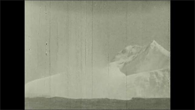 1930s: UNITED STATES: iceberg in sea. North Atlantic ice lanes. Coast guard ship patrols water. Waves crash over deck of ship