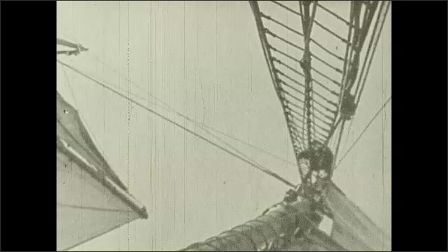 1930s: UNITED STATES: man climbs up rigging on boat. Men run across deck to haul sails. Wake behind boat