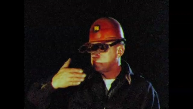 1960s: UNITED STATES: flames in furnace. Man looks at smelter. Man wears protective goggles. Flames inside furnace