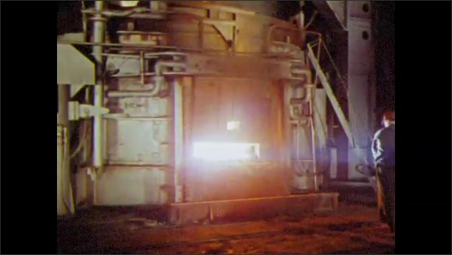 1960s: UNITED STATES: man looks inside furnace. Man shovels metal alloys into furnace. Flames in furnace