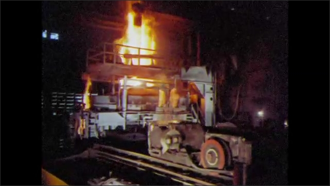 1960s: UNITED STATES: flames escape from furnace. Charging machine removes impurities from steel. Man drives truck. Melter at pouring side of furnace. Man pushes lever