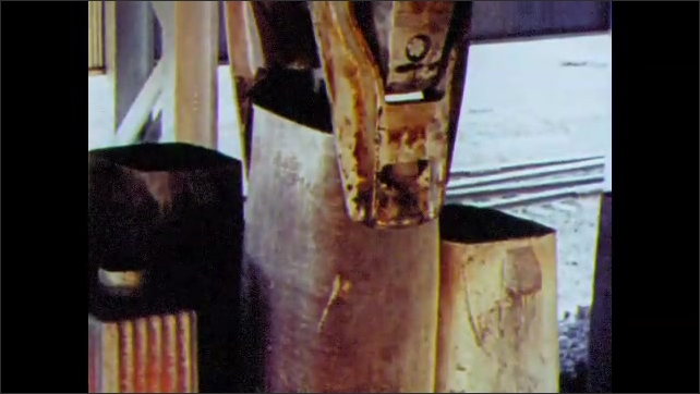1960s: UNITED STATES: hooks remove mold from ingot. Crane lifts metal. Hot ingot.