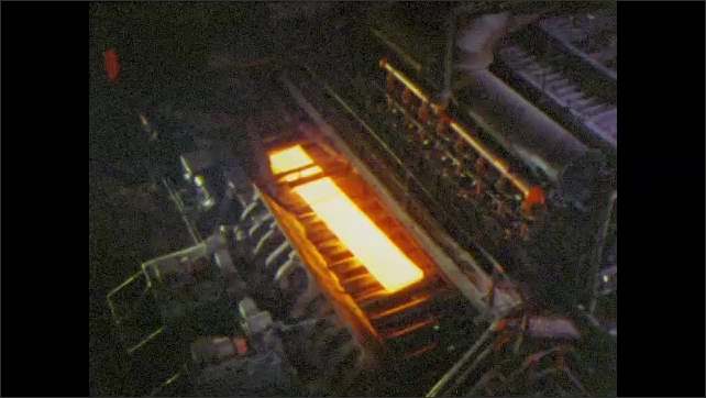 1960s: UNITED STATES: reheat furnace. Steel slab in furnace. Scale breaker. Steam blasts around steel