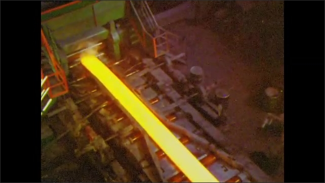 1960s: UNITED STATES: steel slab in roughing process. Steel on conveyor. Steel shaped by rollers. Overhead view of machinery