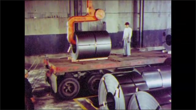 1960s: UNITED STATES: man walks by machines. Temper rolled steel. Galvanized steel. Steel coated with tin. Man oversees steel coil. Hook moves roll of steel