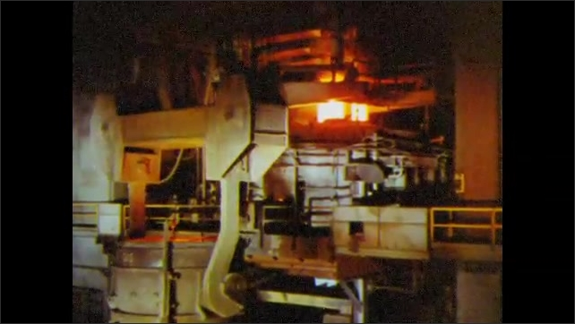 1960s: UNITED STATES: steel production inside mill. Machine moves steel in factory.