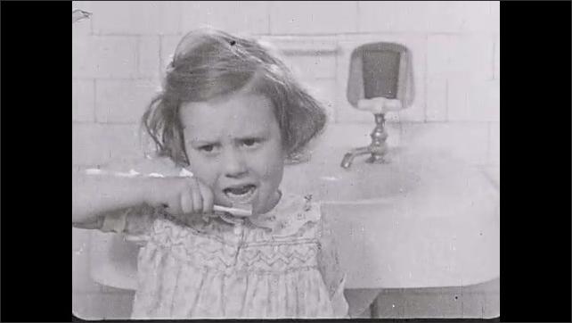 1930s: Woman brushing girl's teeth. Views of girl brushing her own teeth.