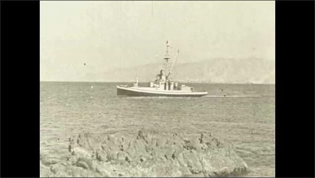 1930s: Fishing boat floats past rocks in ocean bay.
