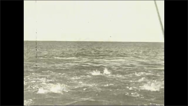 1930s: Fishing boats float out into ocean waves. Fish splash and feed in ocean near fishing boat. Men pull fish from ocean with large fishing rods. Men fish from boat.