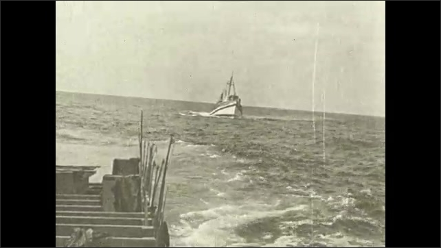1930s: Fishing boats float out into ocean waves.