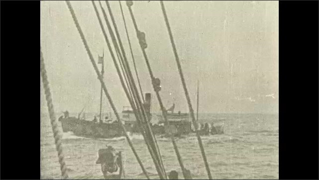 1930s: Fishing boats float out into ocean waves.  Whaling ship passes by boat.
