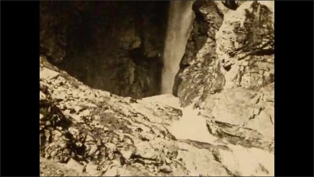 1930s: ALPS: lady sits on mule. Group head up to Mont Blanc viewing point. River runs down rocks