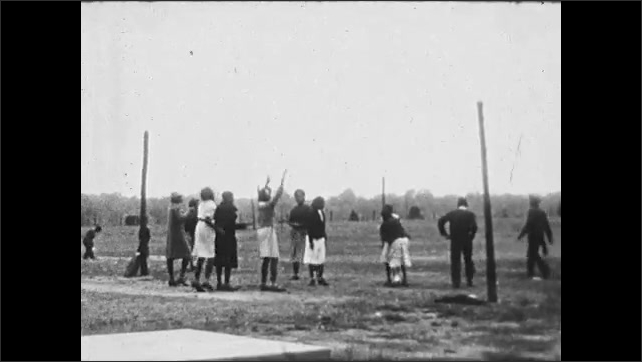 1930s: UNITED STATES: bus and cars parked by high school. Students play with ball outdoors. Students jump for ball.