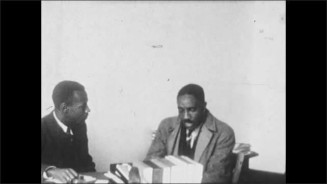 1930s: UNITED STATES: pastors talk in room. Men talk by desk.