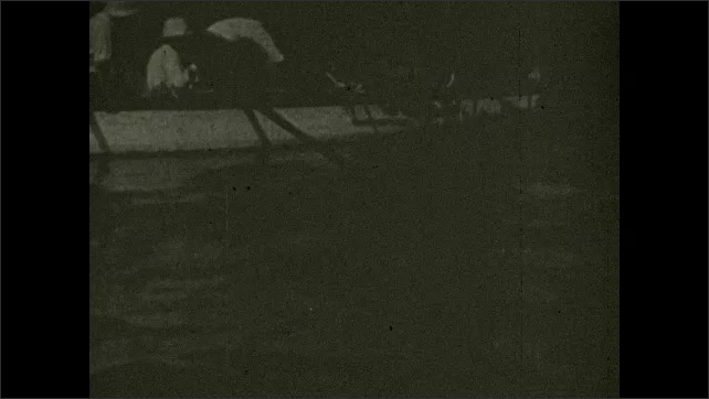 1930s: Title card. Men in row boat, pulling cages from water. Men pull cage onto boat. Man holds fish as other men look at it.