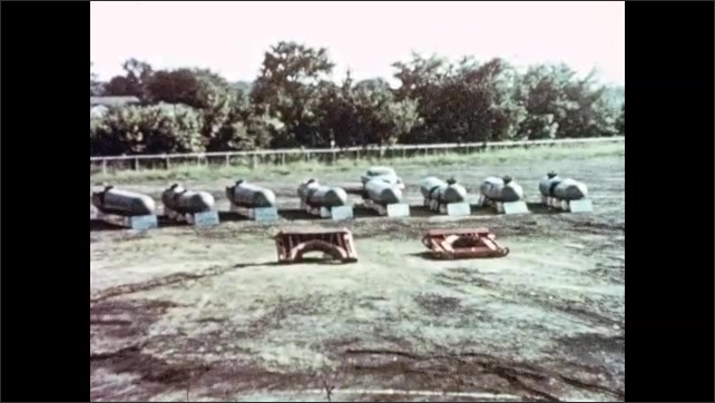 1950s: Signs near demonstration area. Steel pressure vessels in demonstration area. Vessel on stand with sign. Man scrapes frost from frozen pressure vessel.