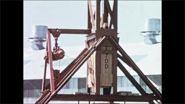 1950s: Workers climb hammer tower. Large weight on tower. Workers observe. Weight rises in tower. Weight slams down on pressure vessel. Frost and ice fall from vessel.  Weight rises.
