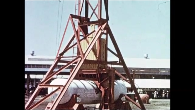 1950s: Weight slams down on pressure vessel. Frost and ice fall from vessel. Men observe damage to pressure vessel. Man with rope climbs hammer tower.