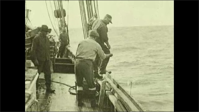 1930s: Hand attaches bait to hook. Man unwinds trawling line. Words on screen. Man tosses weight on rope into ocean. Men prepare dinghies on deck of ship. Men lower dinghy into water.