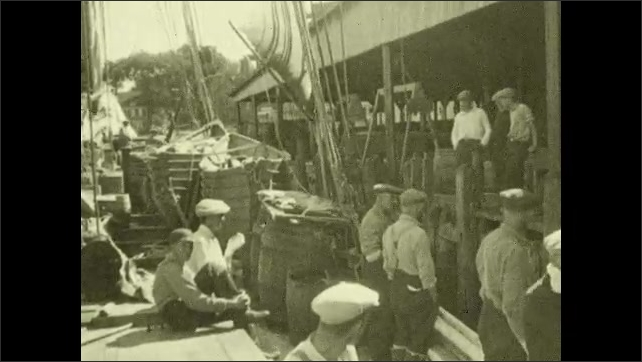 1930s: Men stand on deck of fishing ship. Fishing vessel nestles against dock. Men sit on deck of ship and dock. Tugboat floats past fishing vessel at dock.