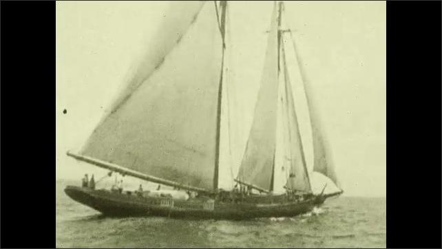 1930s: Sailors turn wheel on ship and prepare sails. Fishing vessel cuts through ocean waves.