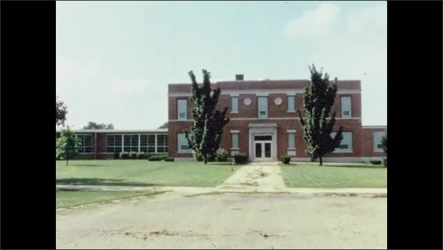 1960s: Exterior of large school building with a bike rack and flag pole. Children line up and approach school.