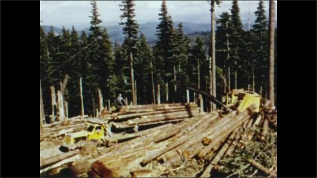 1950s: Heavy equipment picks up log and loads it onto logging truck, dense evergreen forest, mountains in distance. Cables pull felled trees up hill.