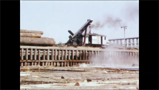 1950s: Train pulls cars of freshly sawn logs over bridge. Logs float in water near bridge. Steam crane pushes logs off train cars into water below.