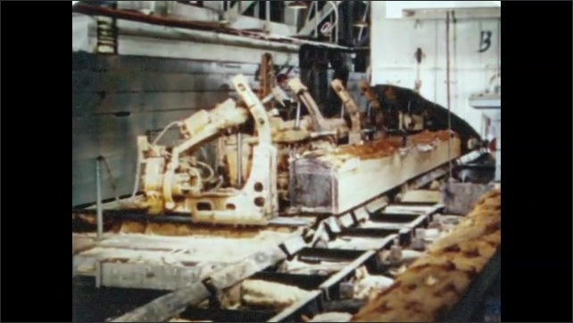 1950s: Workers and machines guide log across saw blades. Strips of log and bark are fall away. Machine flips log over.