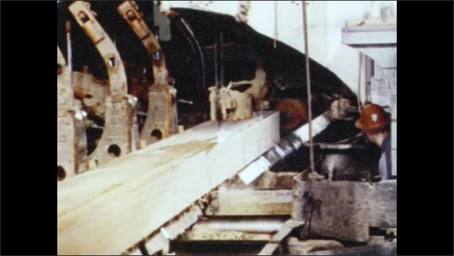 1950s: Workers and machines guide log across saw blades. Strips of log and bark are fall away. Machine and men cut lumber from log. Conveyor belts run alongside saw mill.