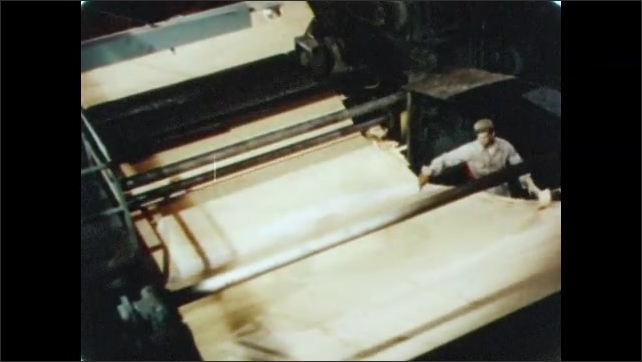 1950s: Log is debarked by industrial machine. Log spins in machine. Sheets of wood are peeled from log. Man guides sheets of wood through machine. Machine cuts sheets of plywood.