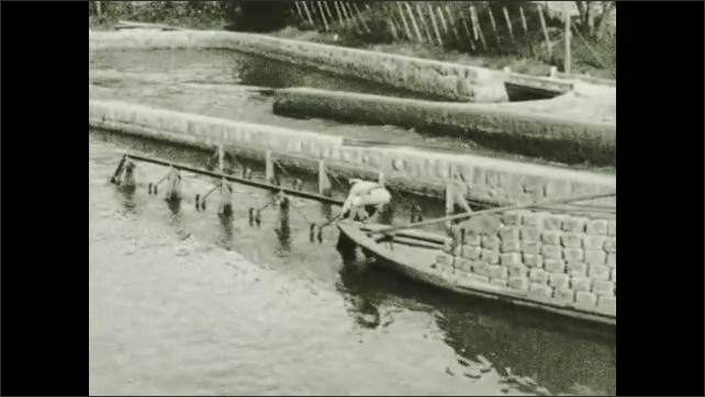1930s: Tracking shot, boat on lift. Views of boat passing through canal. Intertitle. Crowd of people on pier.