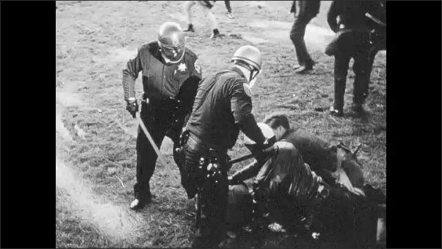 1960s: People run past police officers in crowd. High angle view, officer assaults man. Officers hit man on ground. Officers hit man. Officer runs toward crowd, fights with man.
