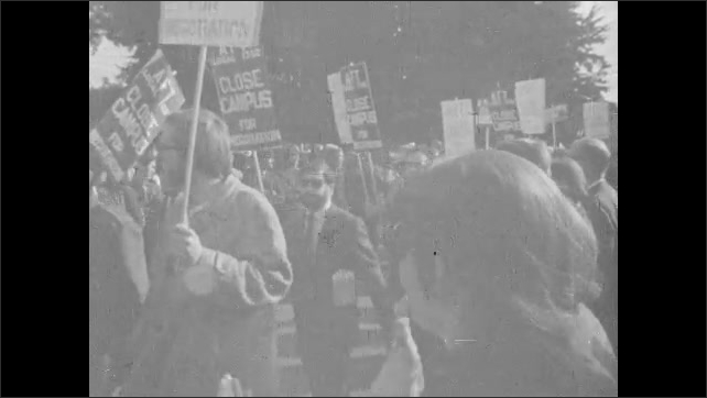 1960s: People marching with signs. Man with sign, tilt up to sign. People march past crowd applauding. Low angle view, people marching.