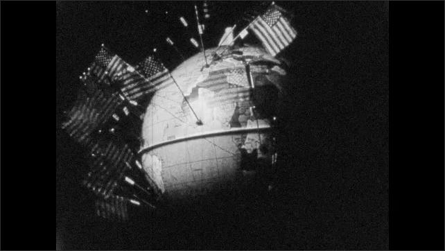 1970s: American flags appear on desk globe. American flag appears on model of moon.