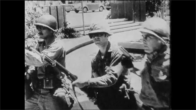 1970s: Police and army soldiers push rioters. Police brandishes gun at rioters. Soldiers with rifles huddle and talk. Soldiers in riot gear line up. Training film intro. People riot in streets.